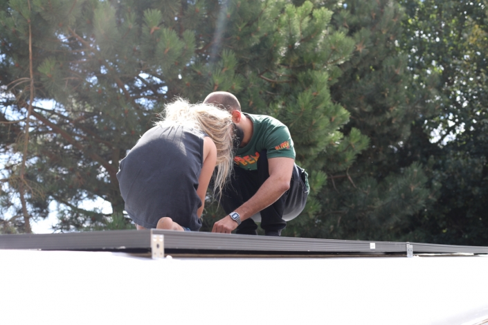 Fjord and Sebatian on the roof, securing the solar panels